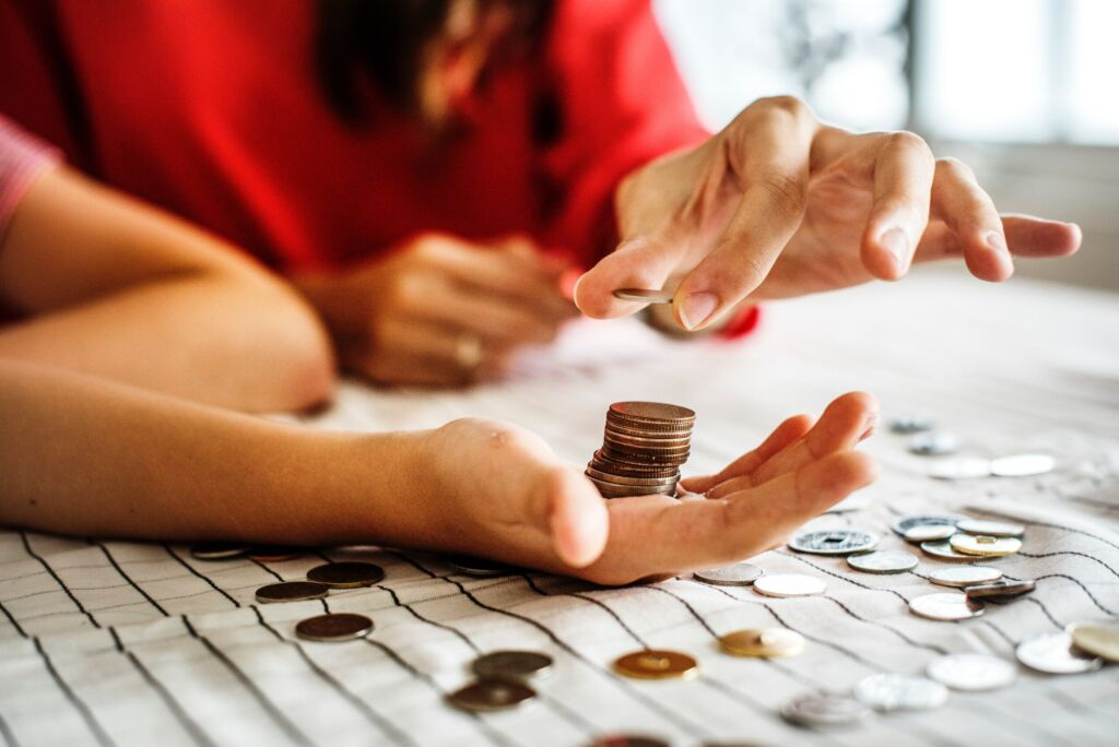 Woman placing one coin on top of coin stack in another woman's hand