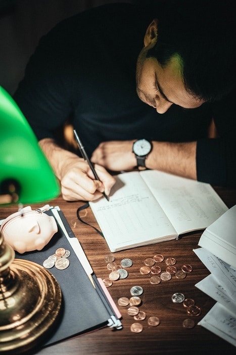 man writing notes with coins on desk