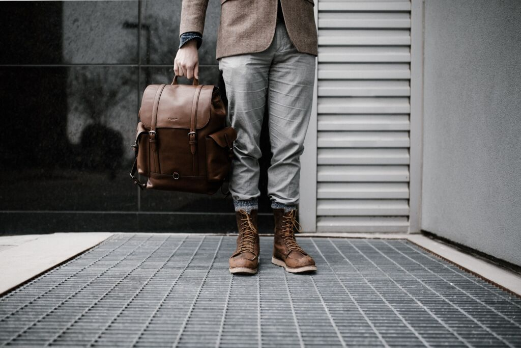 man holding a leather backpack