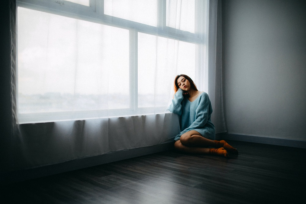 woman sitting on the floor in an empty room