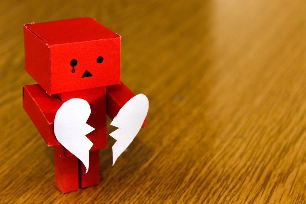paper robot holding a white broken heart