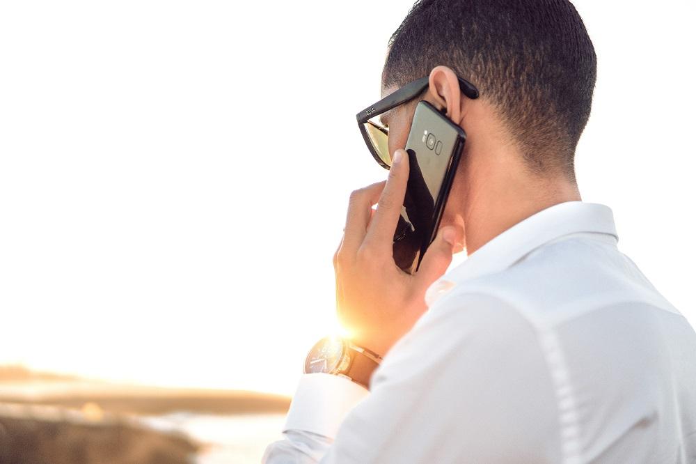 Man wearing white talking on phone