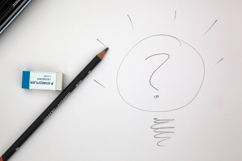 Big question mark drawn inside a light bulb on a white sheet with pencil and eraser