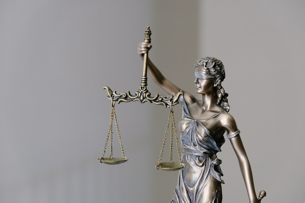 goddess of justice balancing both scales and a sword and wearing a blindfold