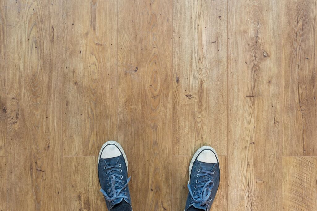 person standing with sneakers on a wooden floor