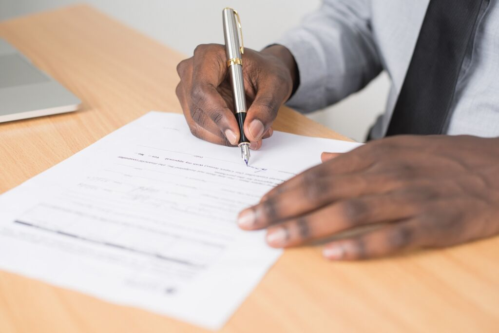 person holding gray twist pen and signing a form