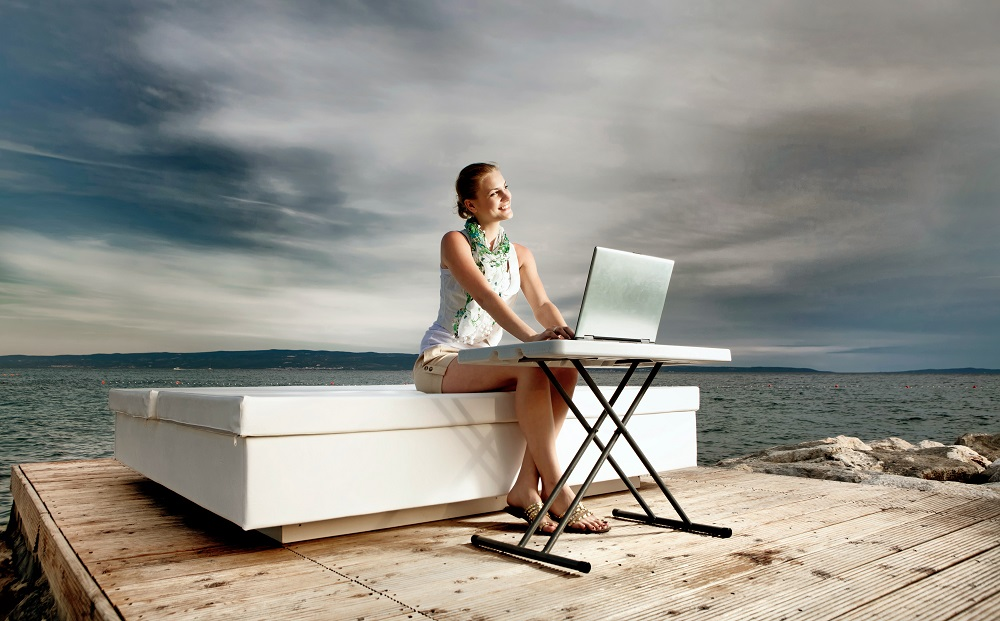 woman on her laptop sitting in front of the ocean