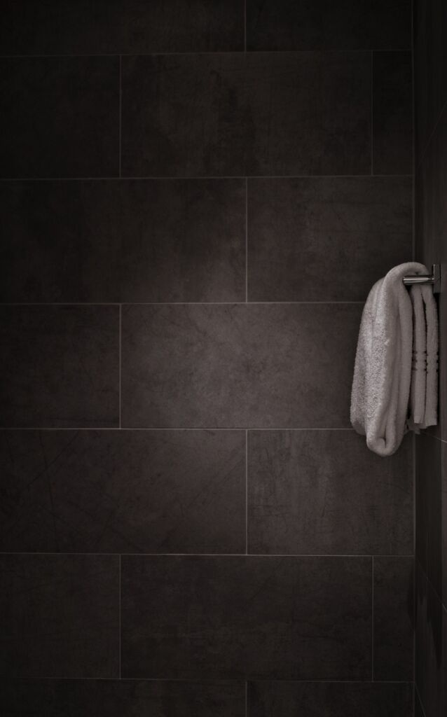dark shower room with a white bath towel on the towel holder