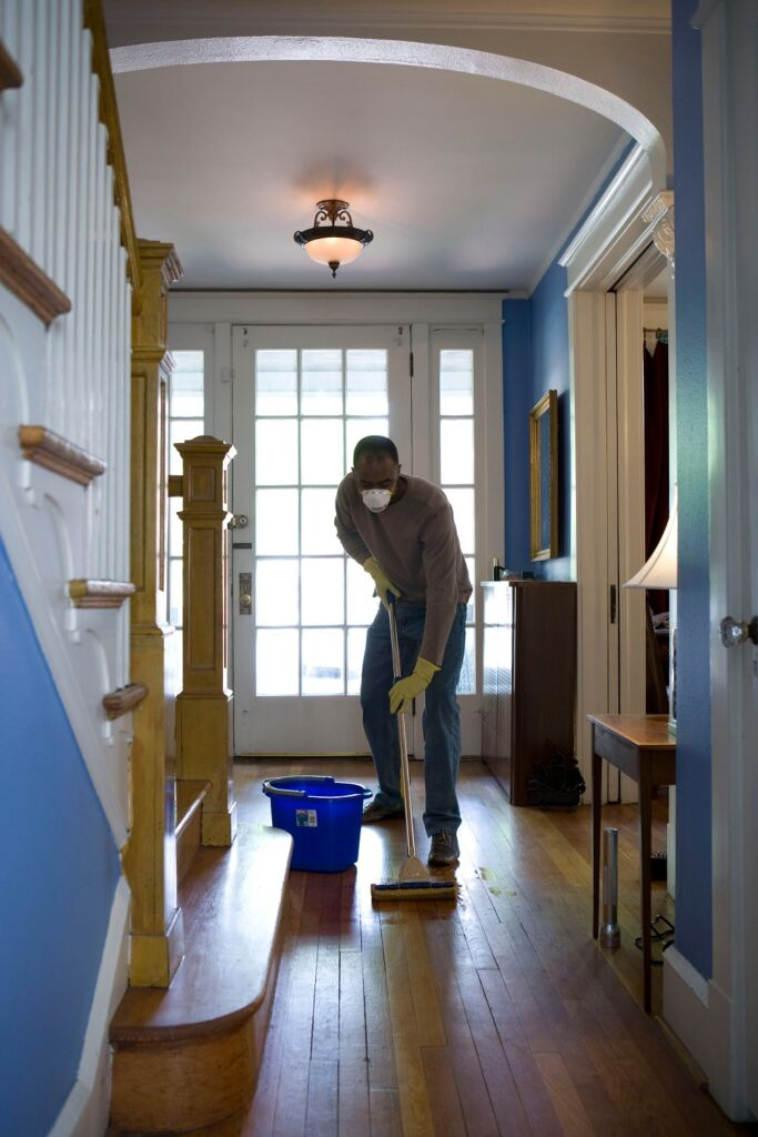 man wearing a mask mopping the floor of the house
