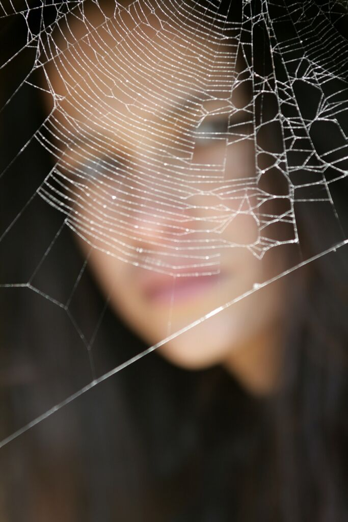 spider web focused with a woman looking behind