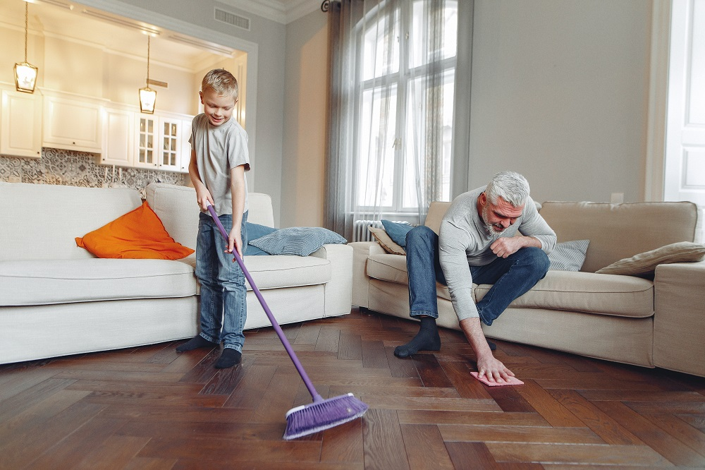 a boy and a man mopping the floor