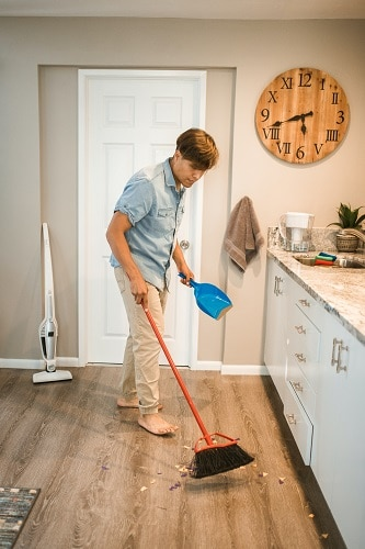 man sweeping floor