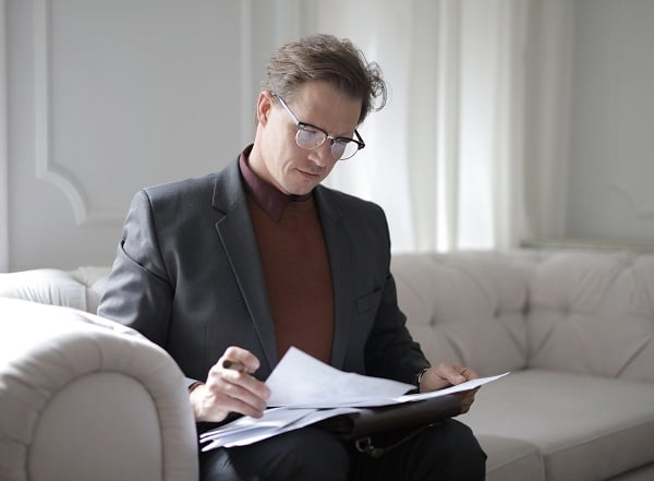 Man reading papers on couch