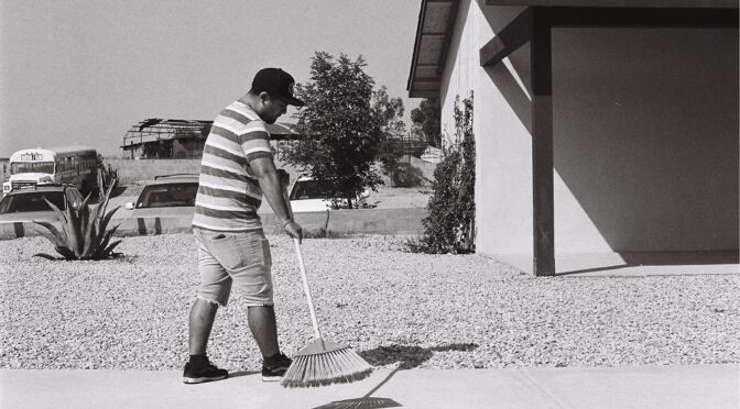 man sweeping the driveway