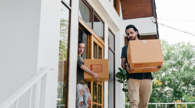 Couple carrying boxes while moving out of old home